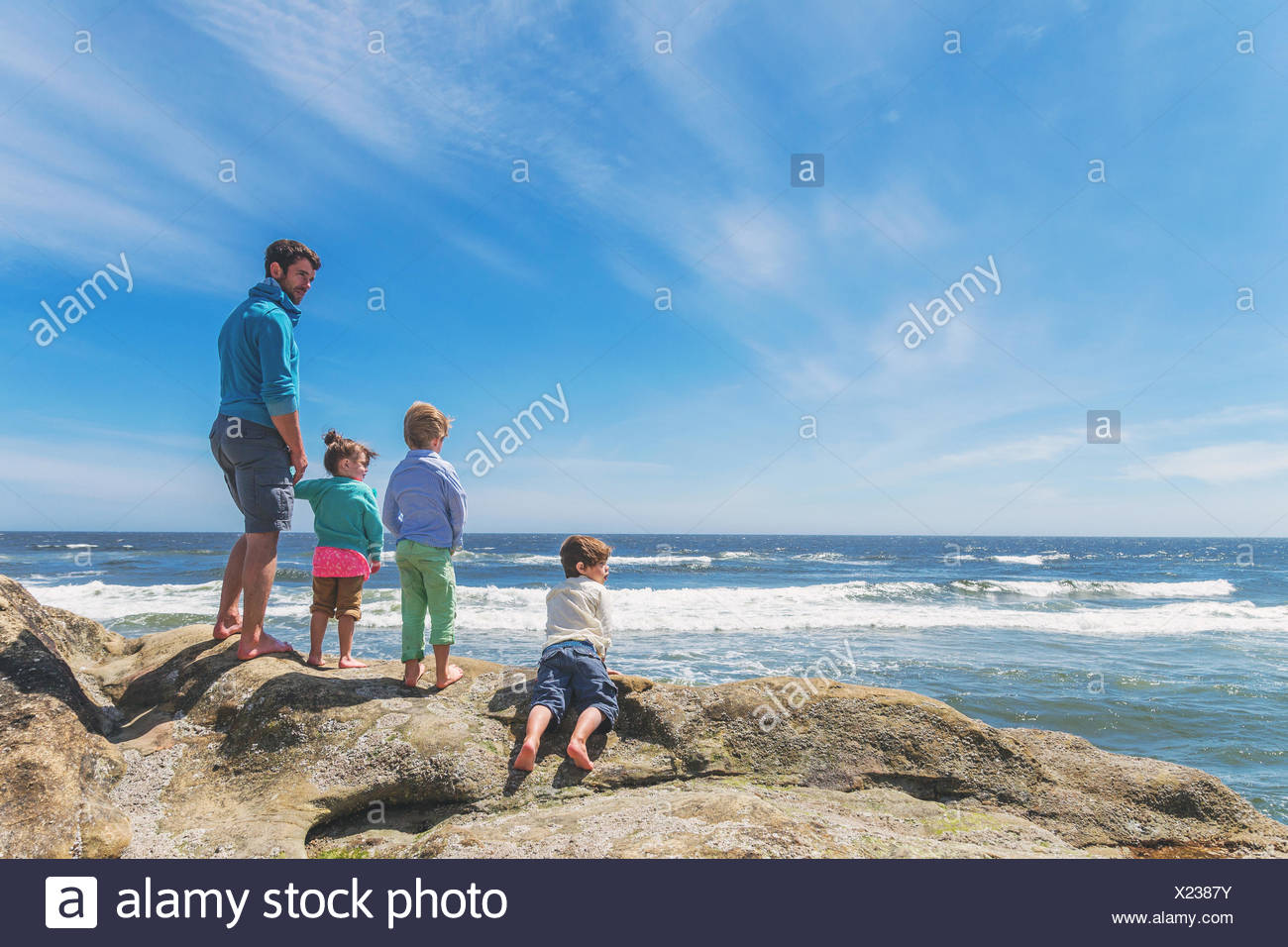 Father and three children on the beach - Stock Image