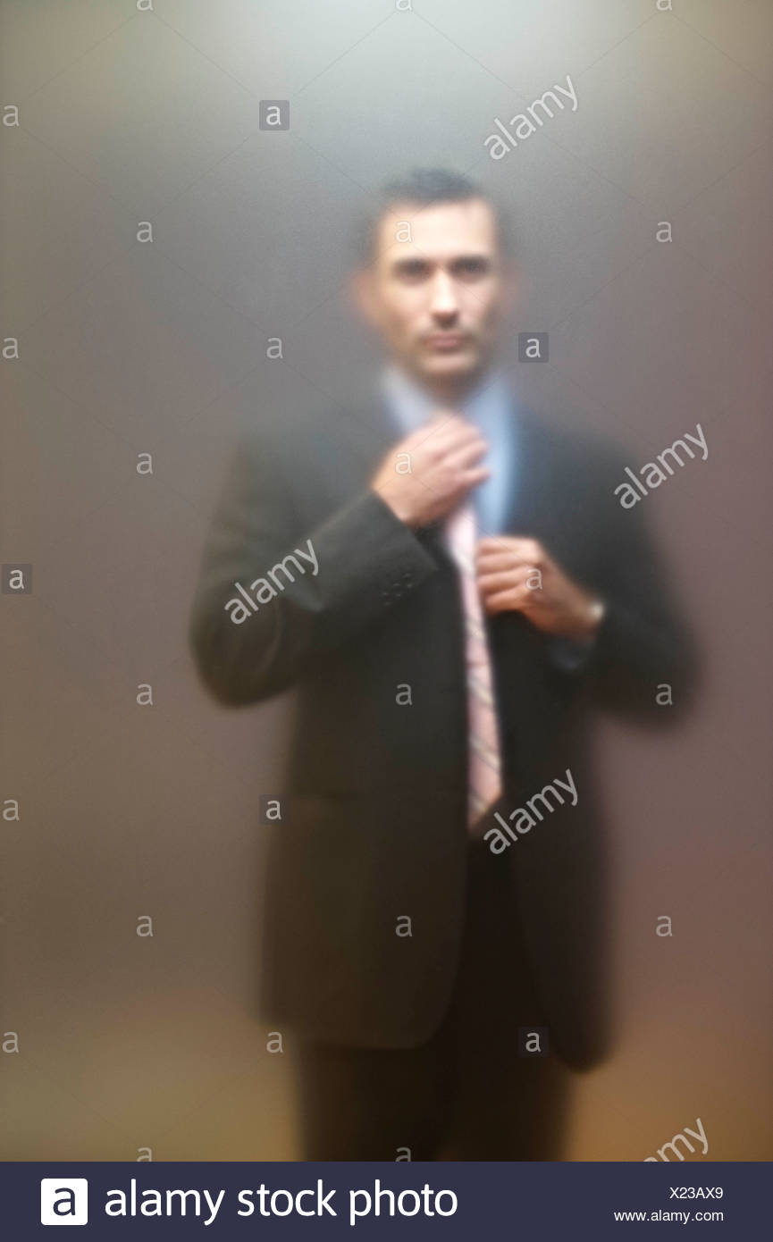 Man adjusting tie behind frosted screen - Stock Image