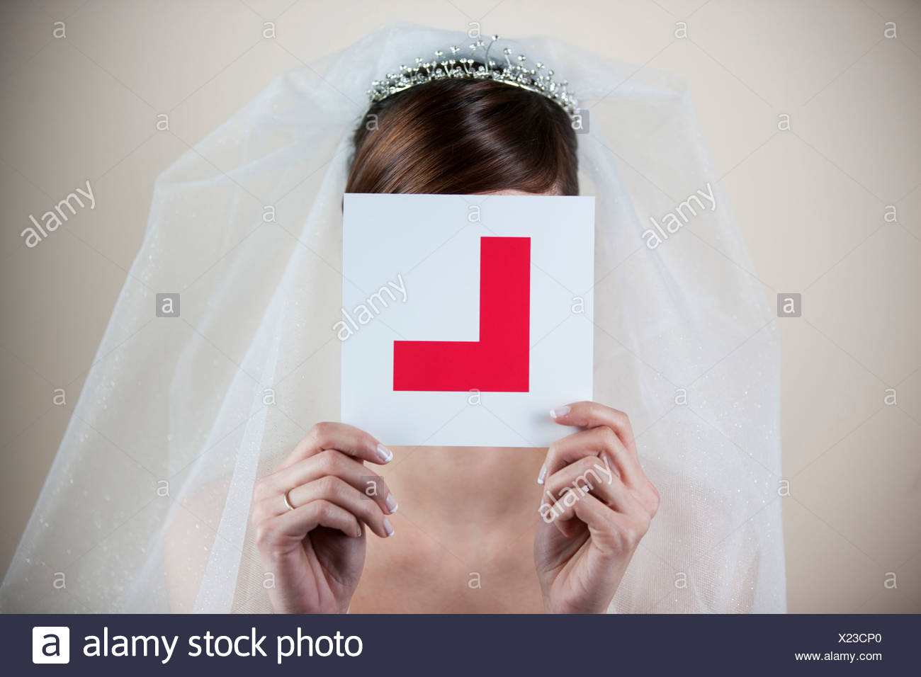 A young bride holding a learner permit plate in front of her face - Stock Image