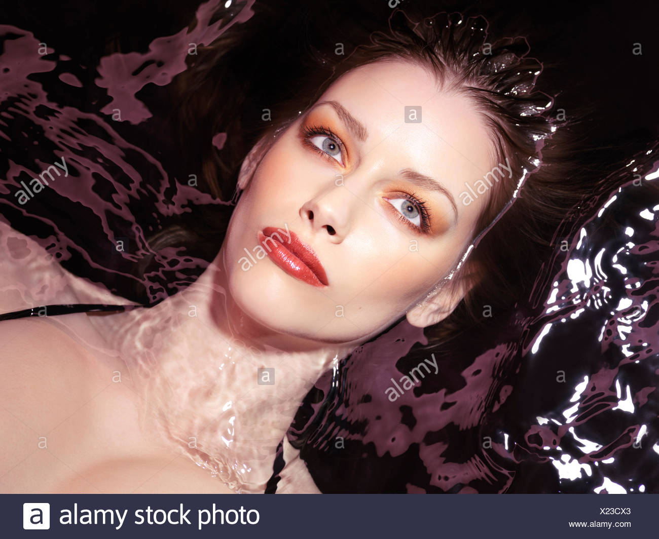 Woman wearing makeup lying in dark water - Stock Image