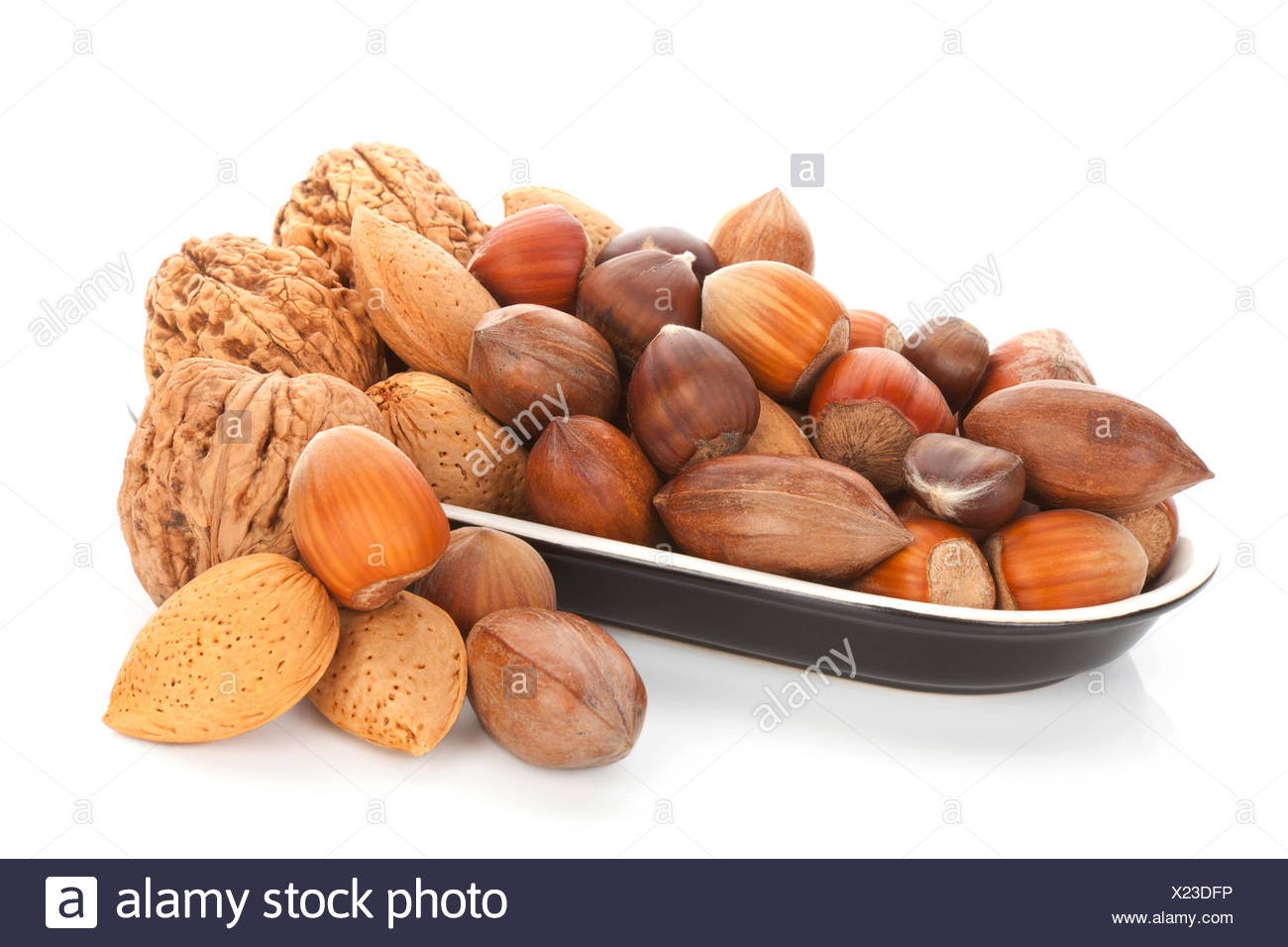 Various nuts in bowl isolated on white. - Stock Image