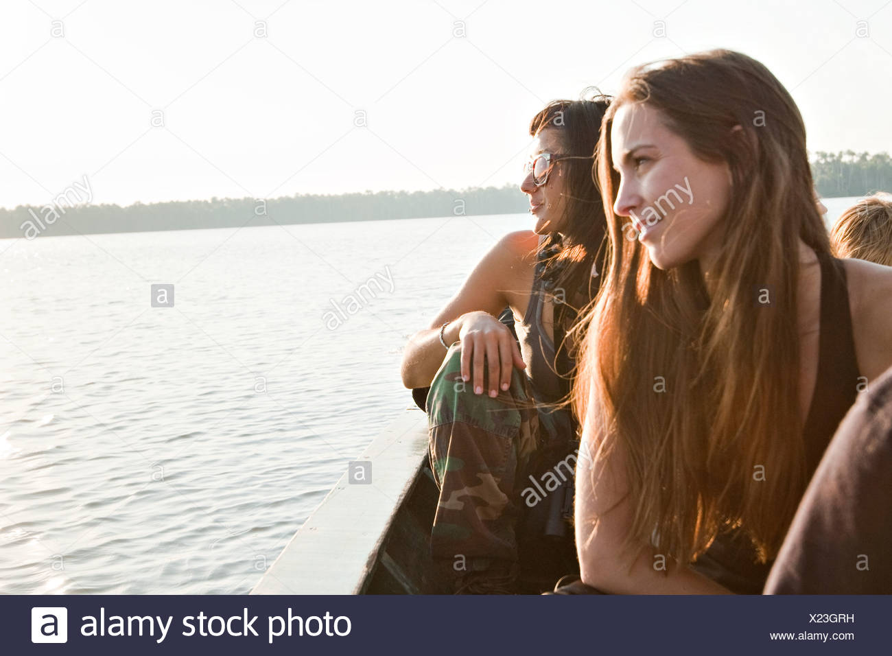 Two young women look into the sunset over Lake Sandoval, in the amazon rainforest. - Stock Image