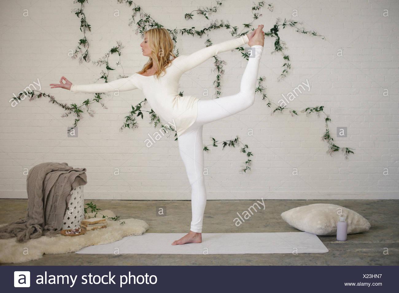 A blonde woman in a white leotard and leggings, standing on a white mat in a room, standing on one leg and arms outstretched. - Stock Image
