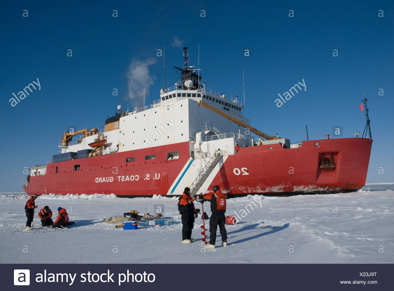 Alaska, Bering Sea. Scientents disembark from a US Coast Guard icebreaker to perform ice-coring tests on the pack ice. Winter. - Stock Image