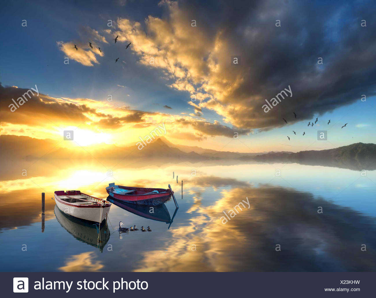Two rowboats anchored in calm sea at sunrise - Stock Image