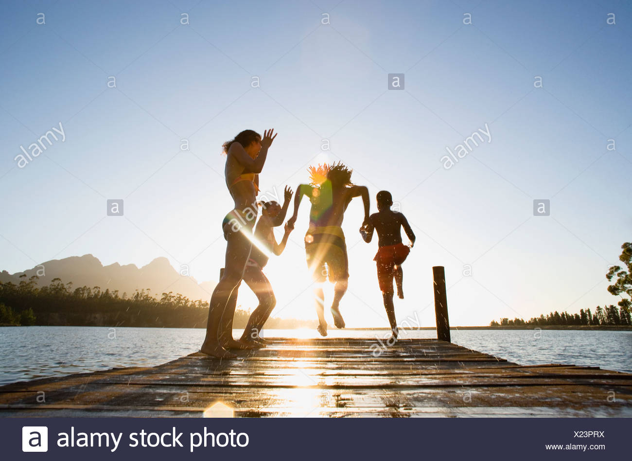 Family in swimwear running along jetty jumping into lake at sunset rear view surface level lens flare - Stock Image