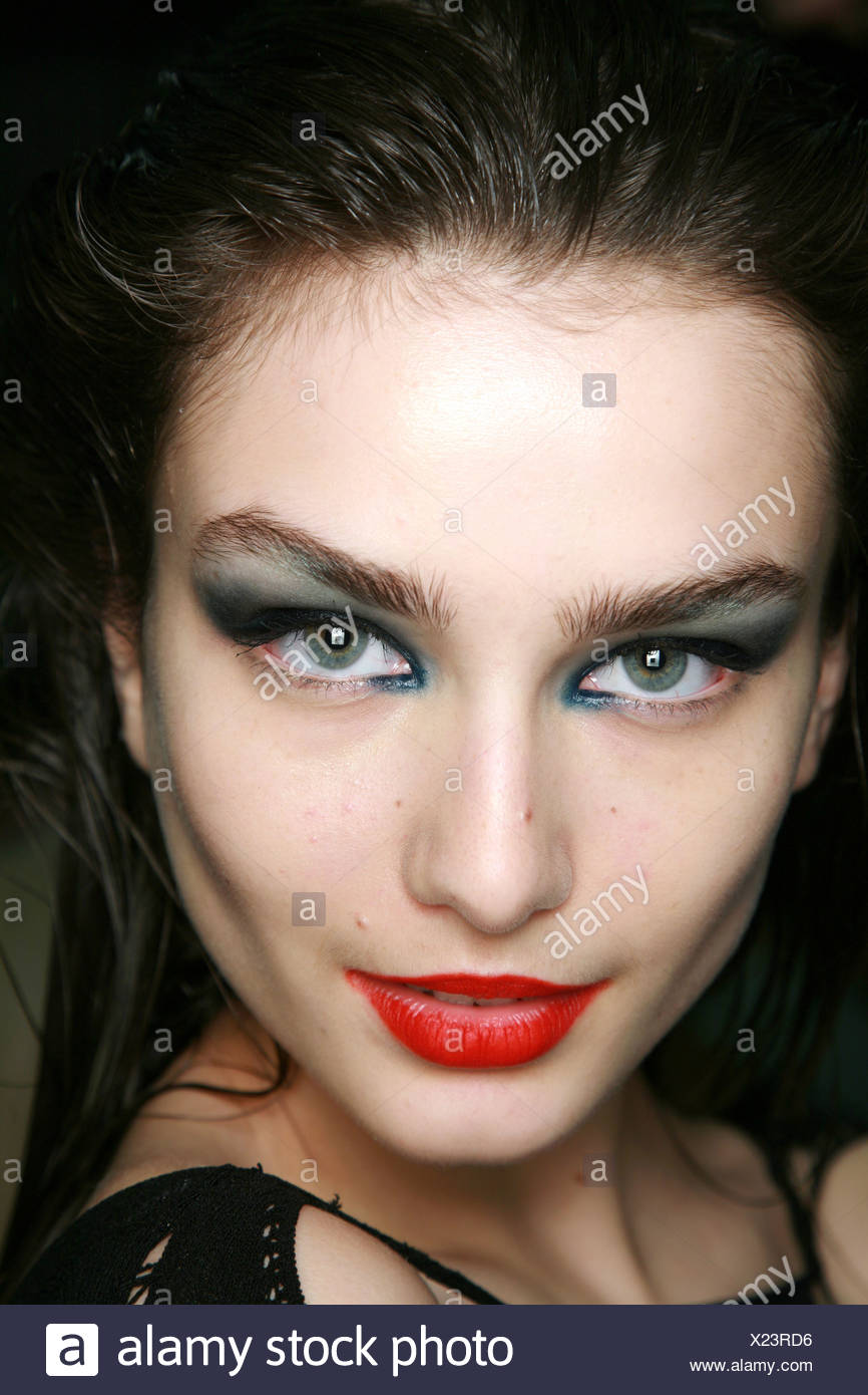 Mark Fast Backstage London Ready to Wear Autumn Winter Close up face of brunette green two tone eyeshadow, and bright red - Stock Image