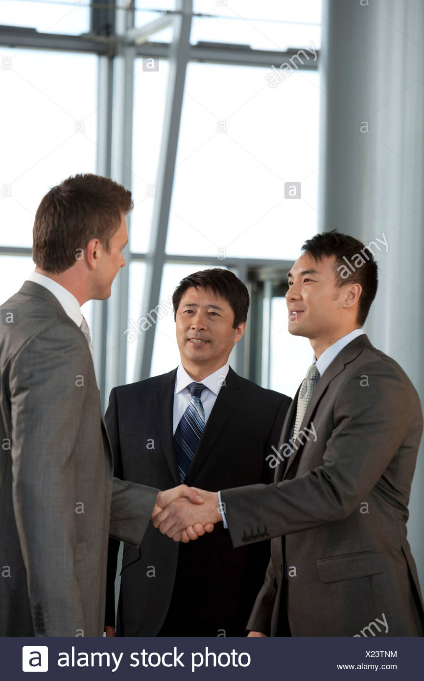 Multiracial businessmen shaking hands - Stock Image