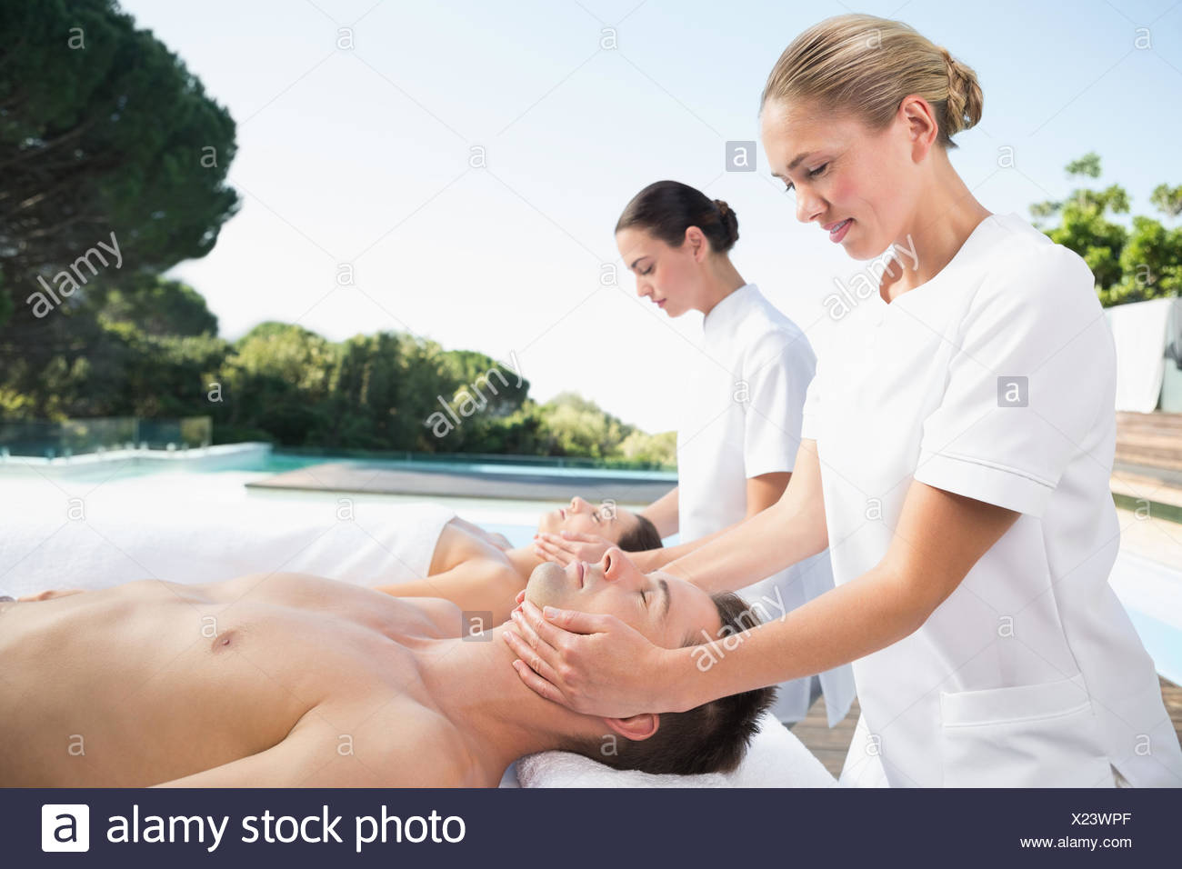 Content couple enjoying head massages poolside - Stock Image