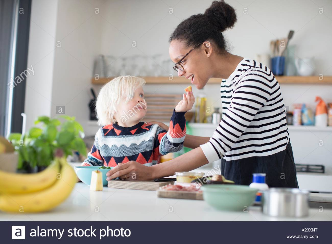 Son feeding mother food in kitchen - Stock Image
