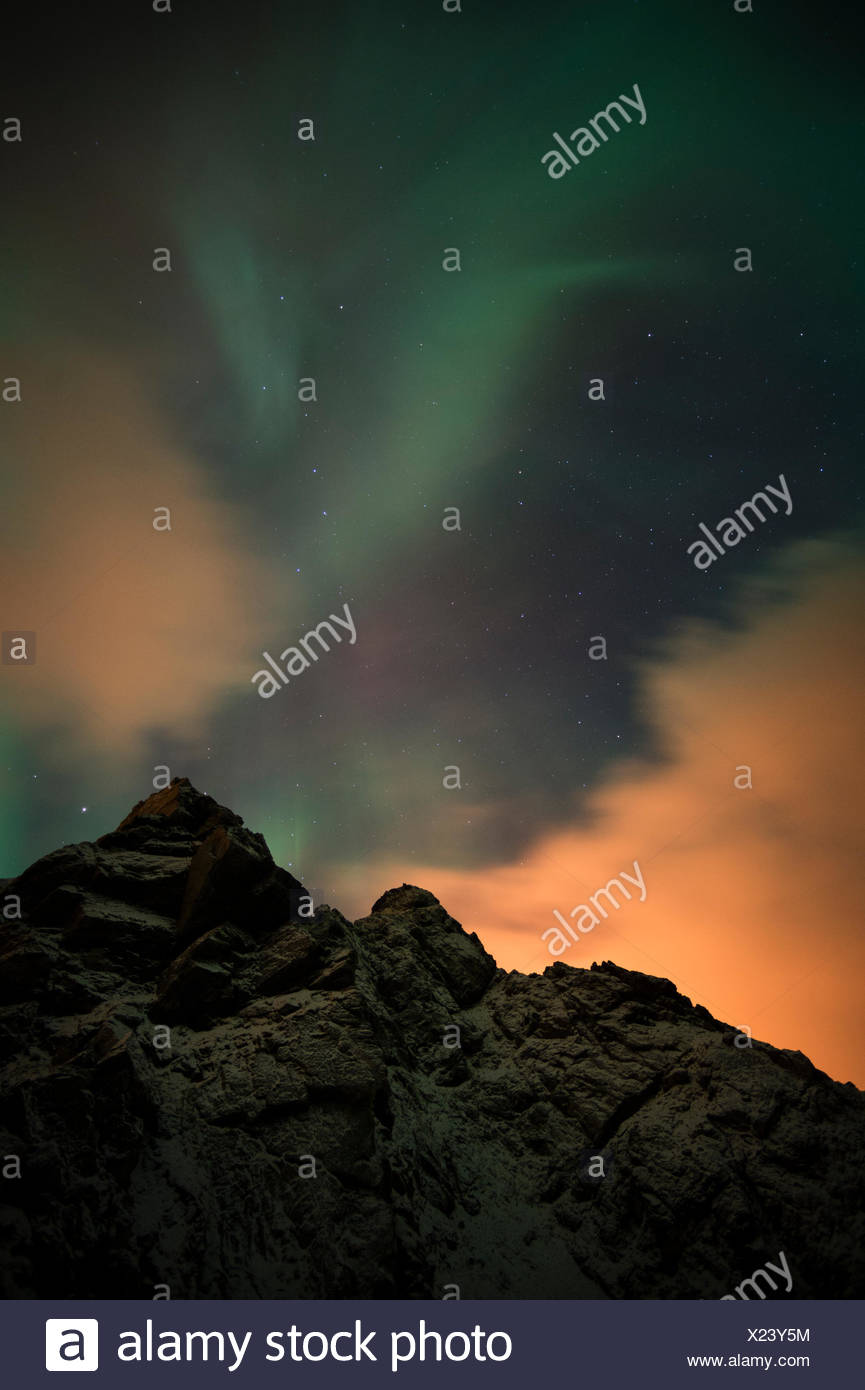 An aurora borealis and the Big Dipper constellation above a mountain peak. - Stock Image