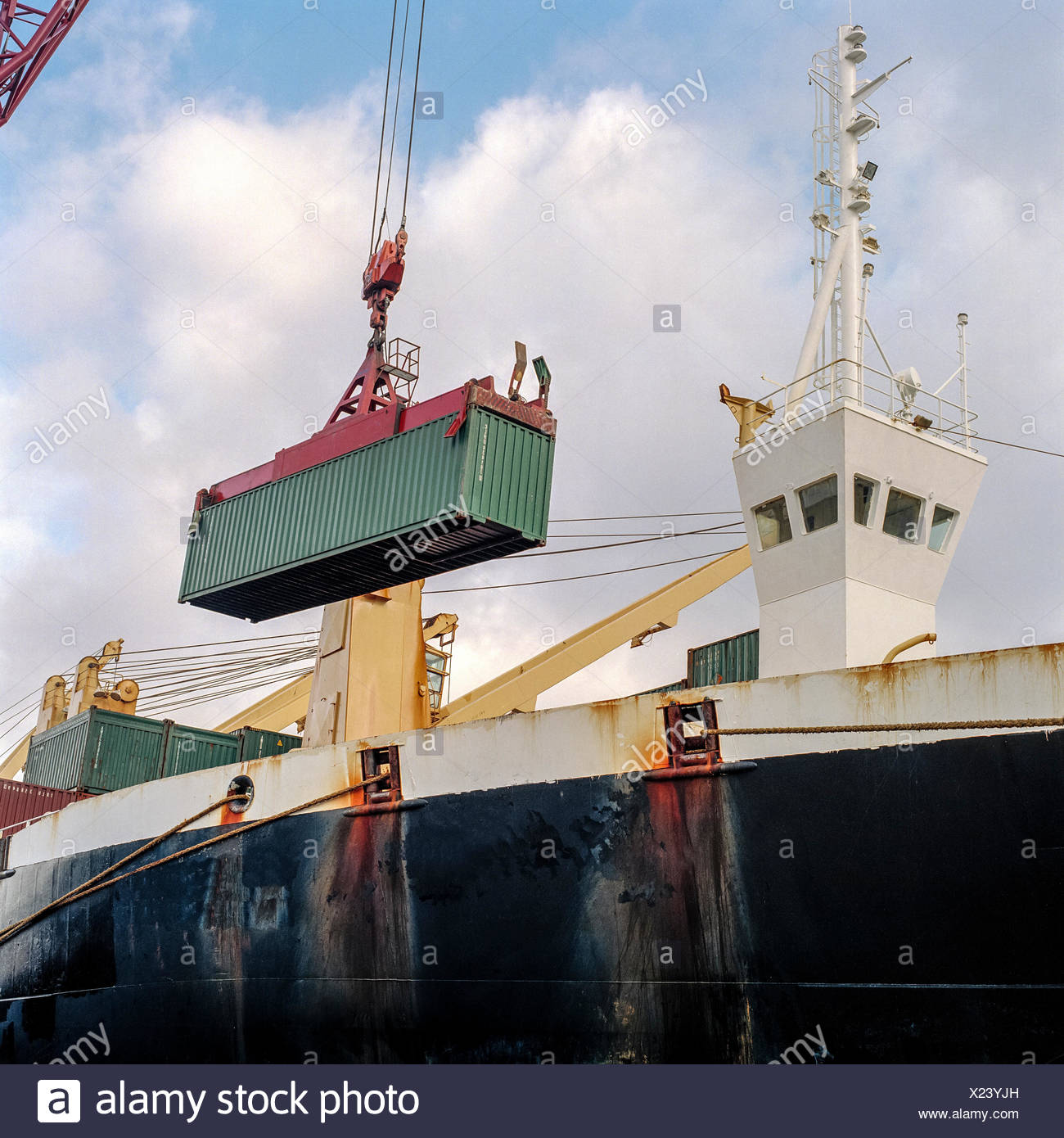 Shipping container being lowered by crane onto ship in port - Stock Image