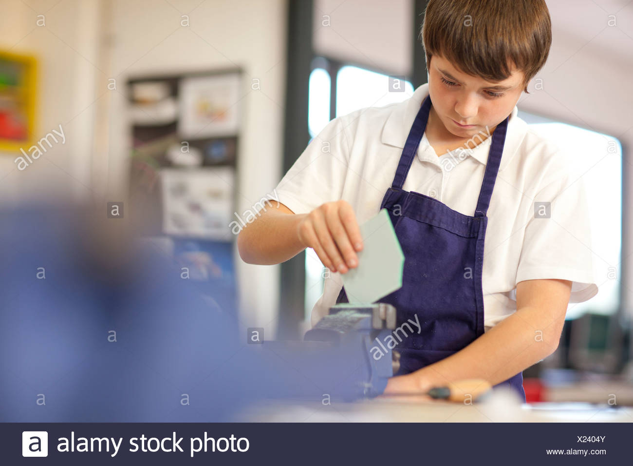 Boy using vice in school workshop - Stock Image