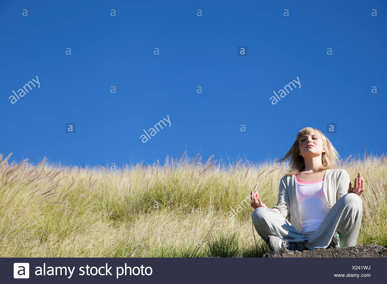 Young woman in yoga position on grassy hill - Stock Image