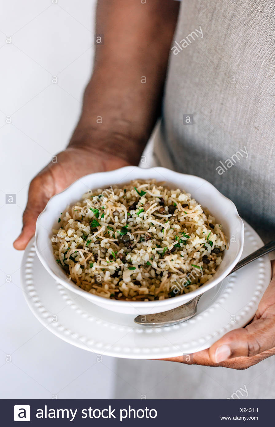 A bowl of bulgur pilaf mixed in with lentils and fresh herbs are in the hands of a man wearing an apron. - Stock Image