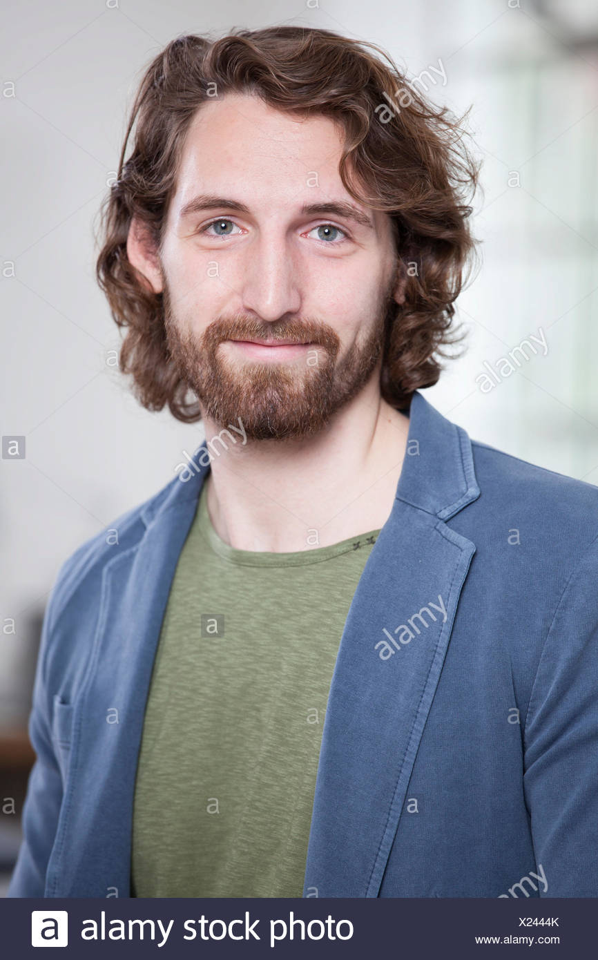Portrait of smiling young man wearing full beard - Stock Image