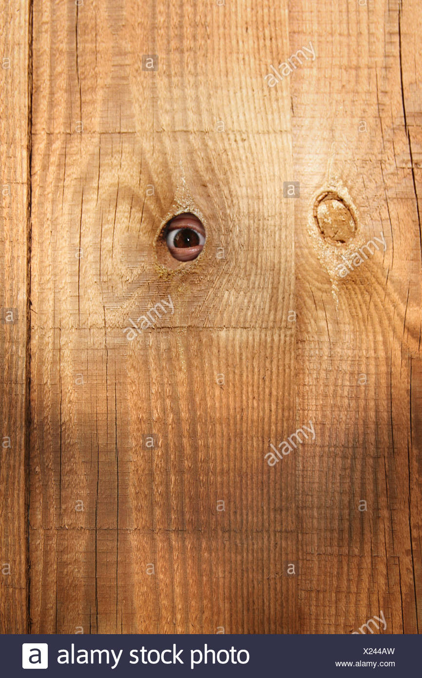 somebody peeping through a hole in the fence - Stock Image