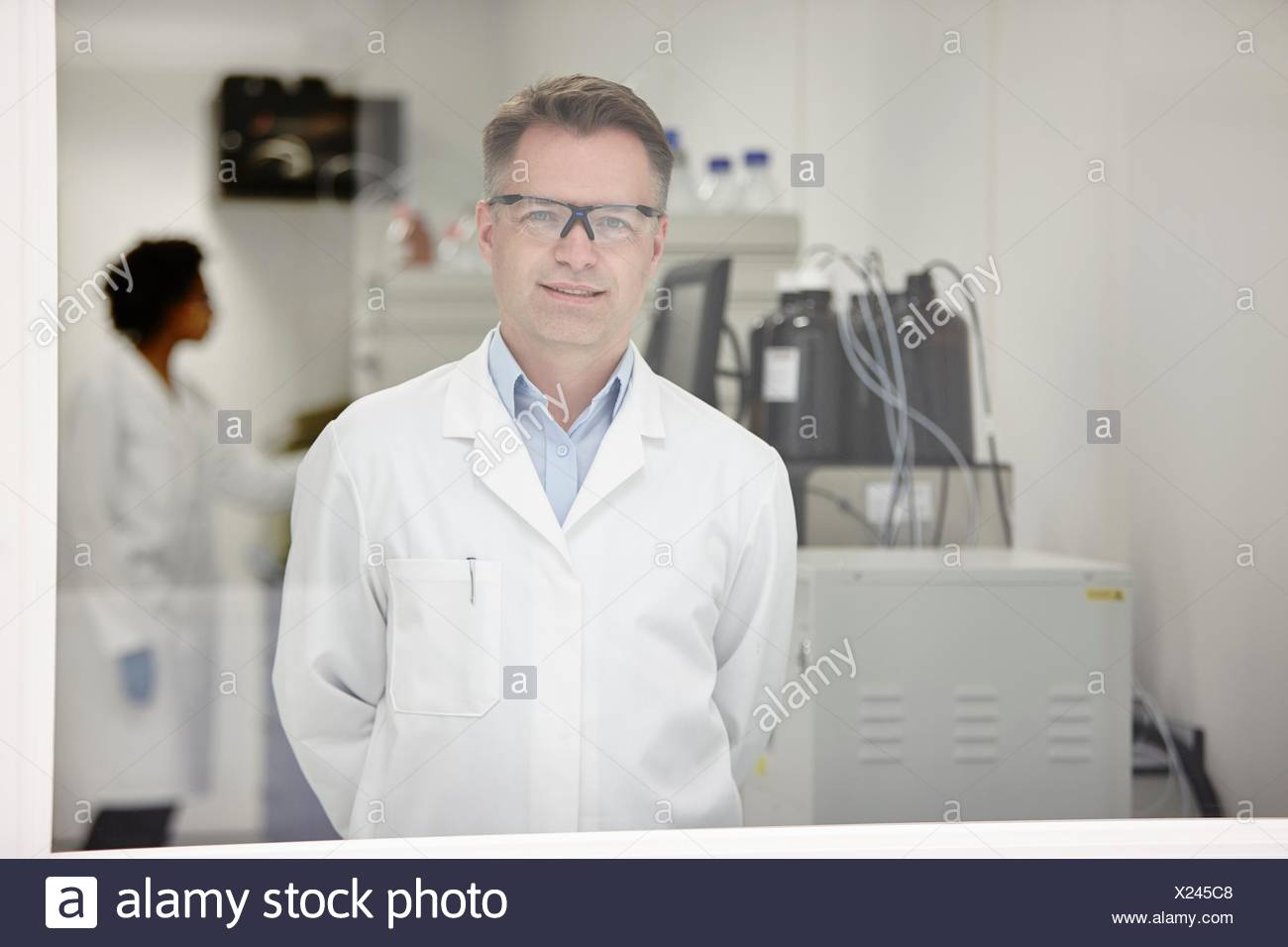 Scientist smiling in laboratory, colleague working in background - Stock Image