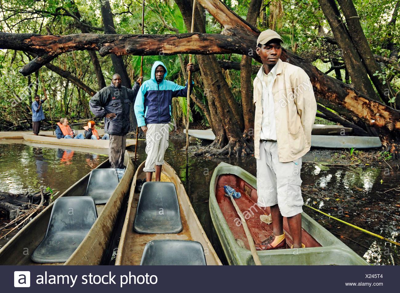 Guides and boatmen, with pole on mokoro or makoro canoes, Okavango Delta, Botswana, Africa - Stock Image