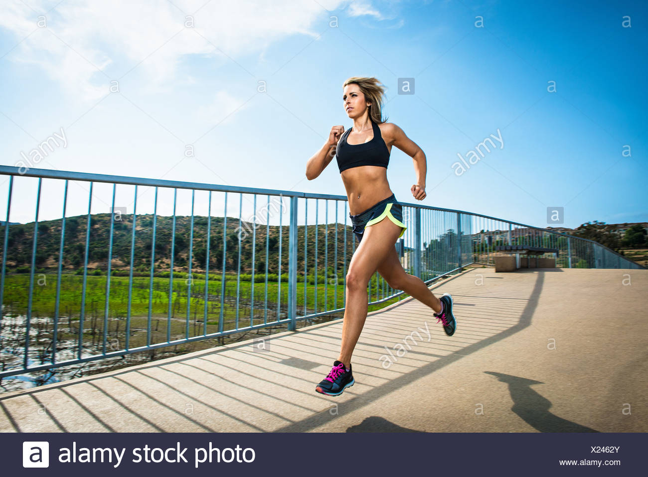 Athletic woman running on bridge - Stock Image