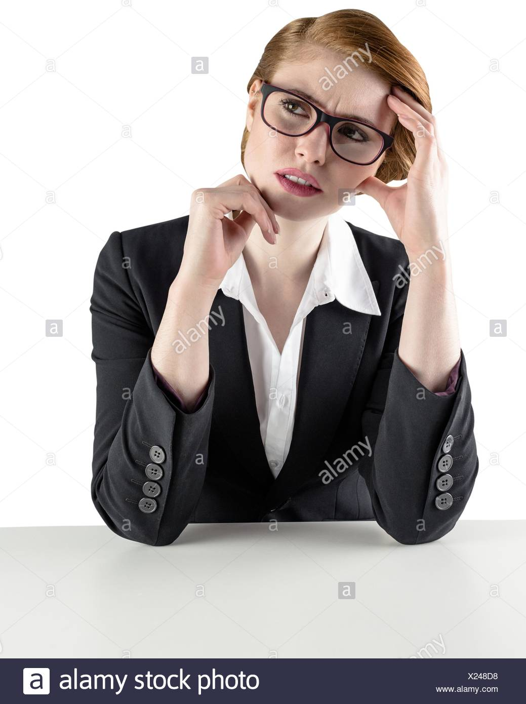 Thinking redhead businesswoman looking puzzled - Stock Image