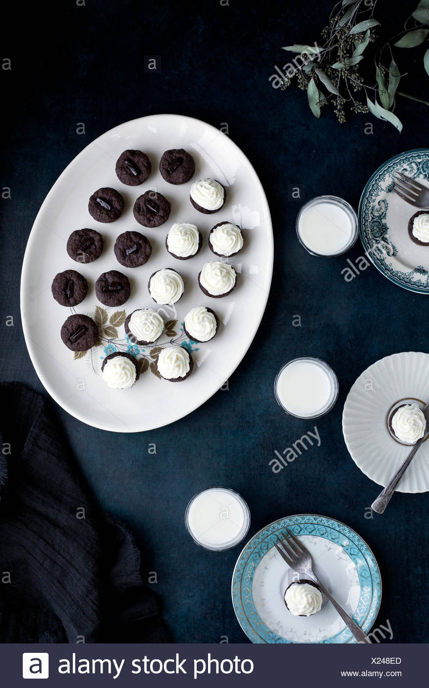 Brownie Bites with Orange Blossom Mascarpone Frosting served with milk.  Photographed on a dark blue background. - Stock Image