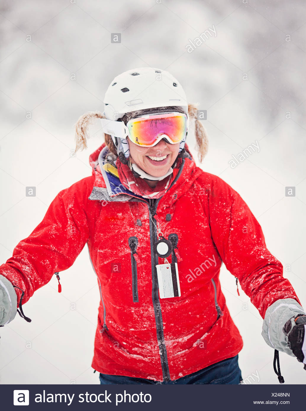 A female skier with her braids tucked into her goggle straps. - Stock Image