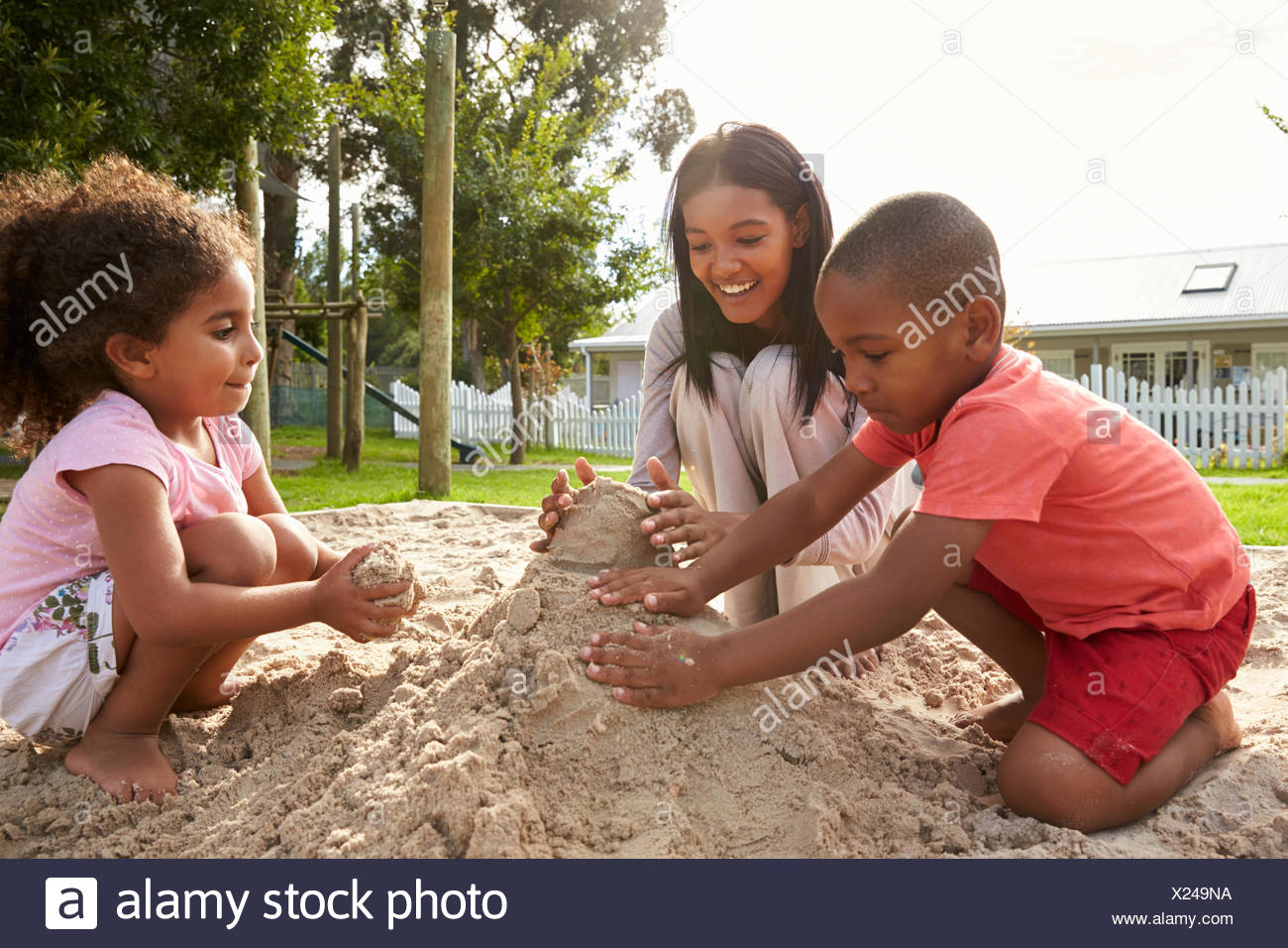 Teacher At Montessori School Playing With Children In Sand Pit - Stock Image