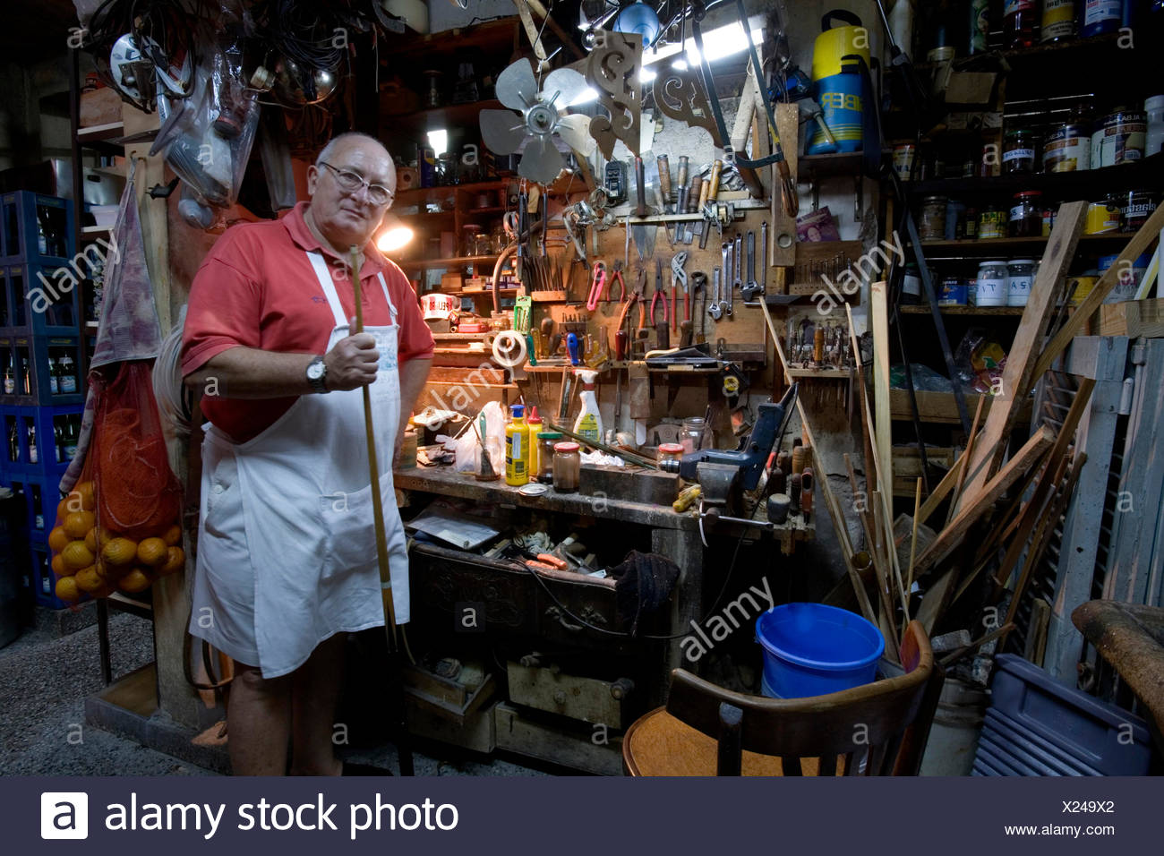 guy in a workshop toolshed with a billiard cue, Argentina - Stock Image