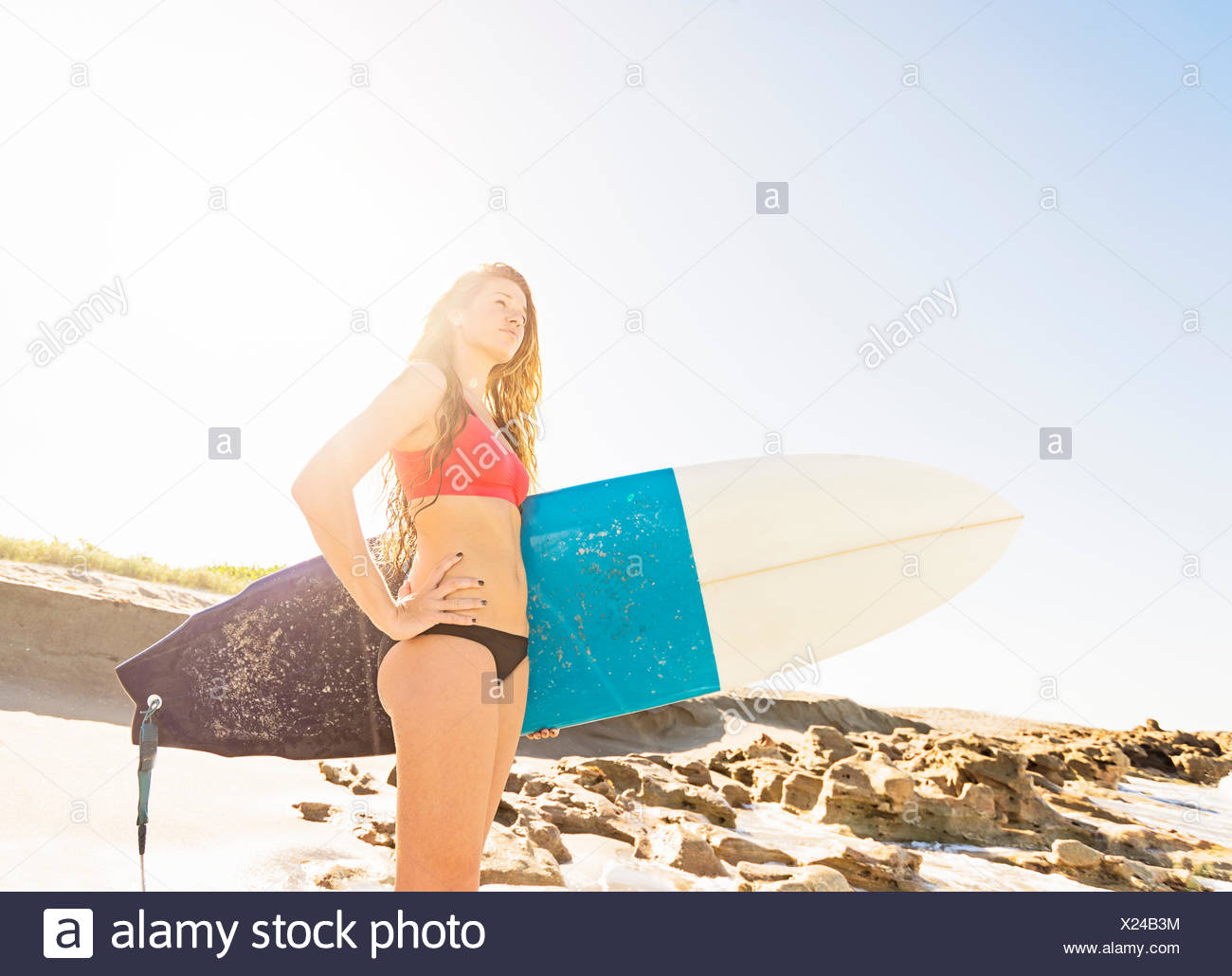 USA, Florida, Jupiter, Portrait of young woman standing on beach, holding surfboard - Stock Image