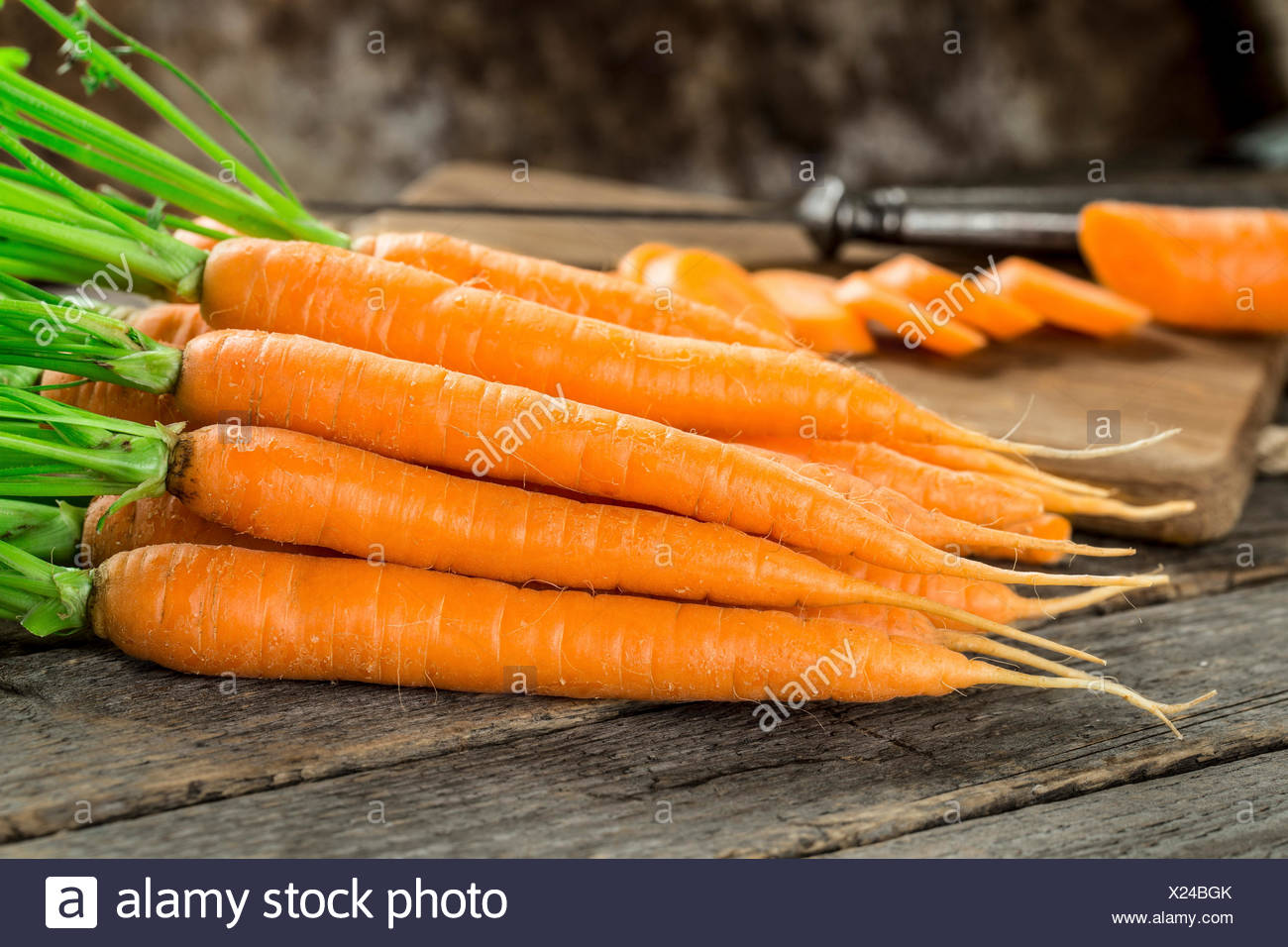 Fresh and sweet carrot on a grey wooden table - Stock Image