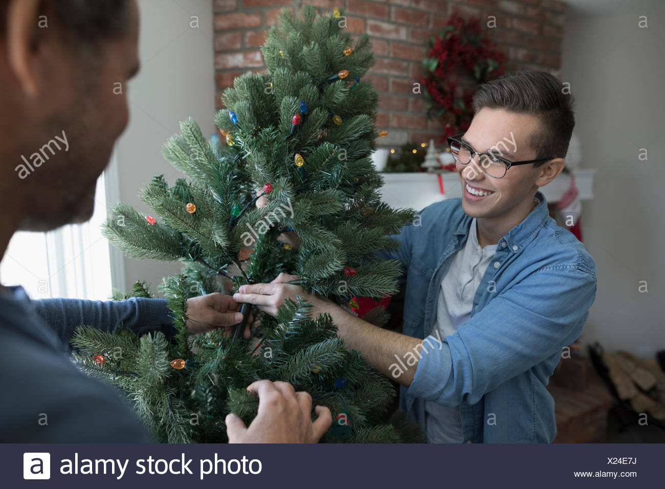 Father and son decorating, assembling artificial Christmas tree in living room - Stock Image