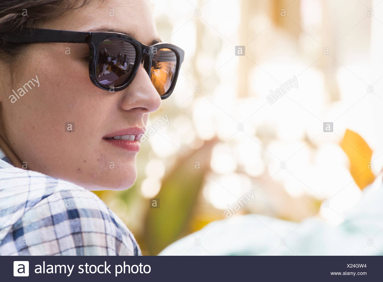 A young woman wearing sunglasses turning towards a man. - Stock Image