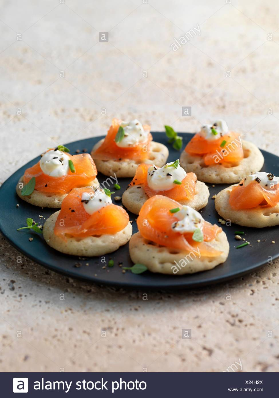 Smoked salmon and cream cheese on blinis with chive and black pepper garnish - Stock Image
