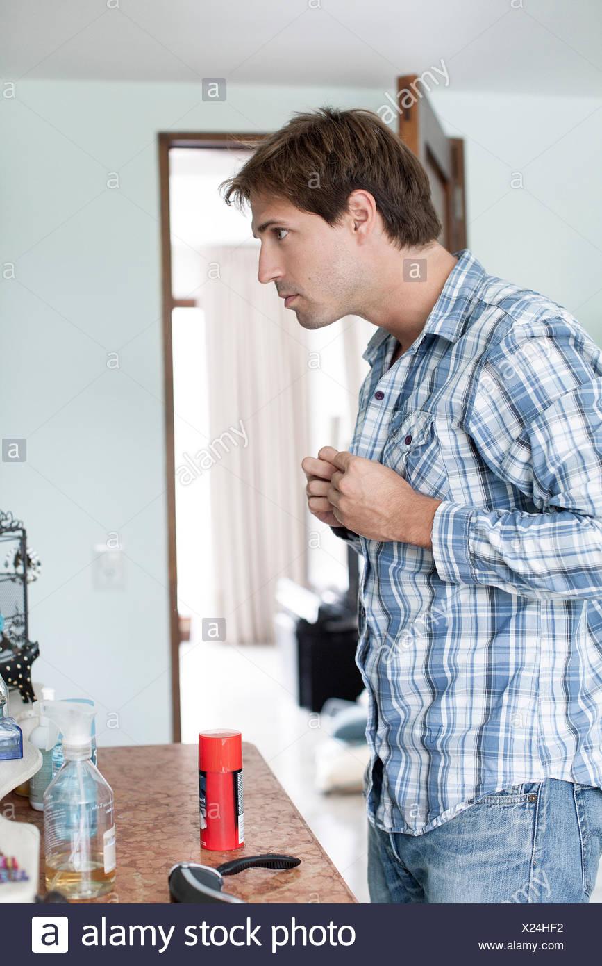 Man buttoning shirt - Stock Image