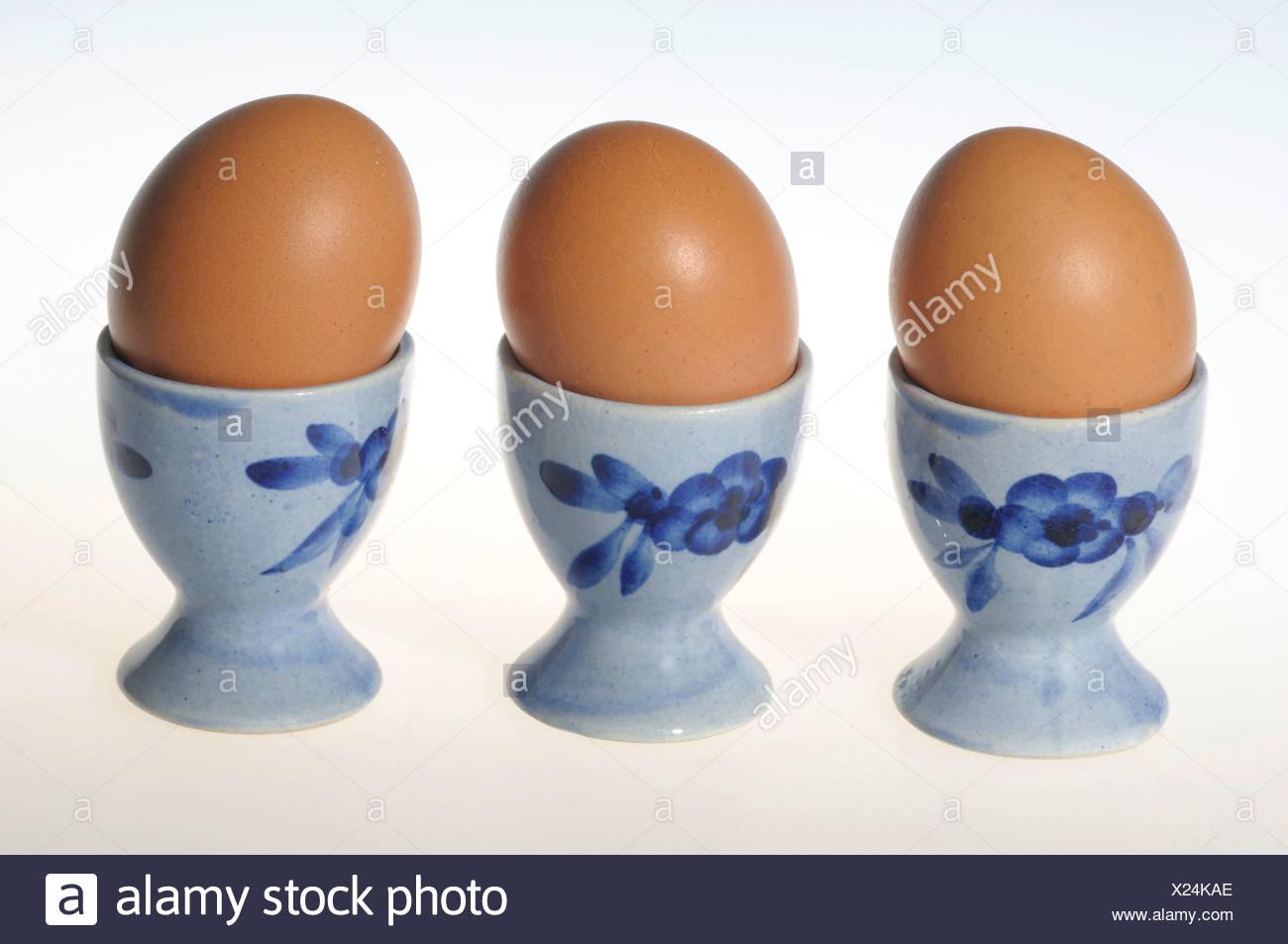hen's eggs in egg cups - Stock Image