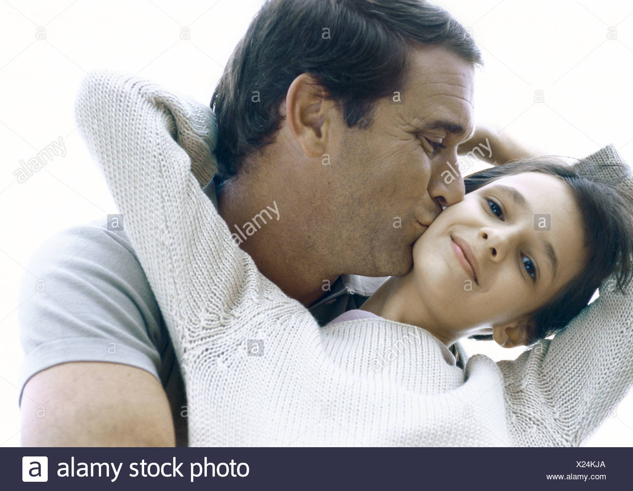 Girl reaching arms back around father's neck, father kissing girl's cheek - Stock Image