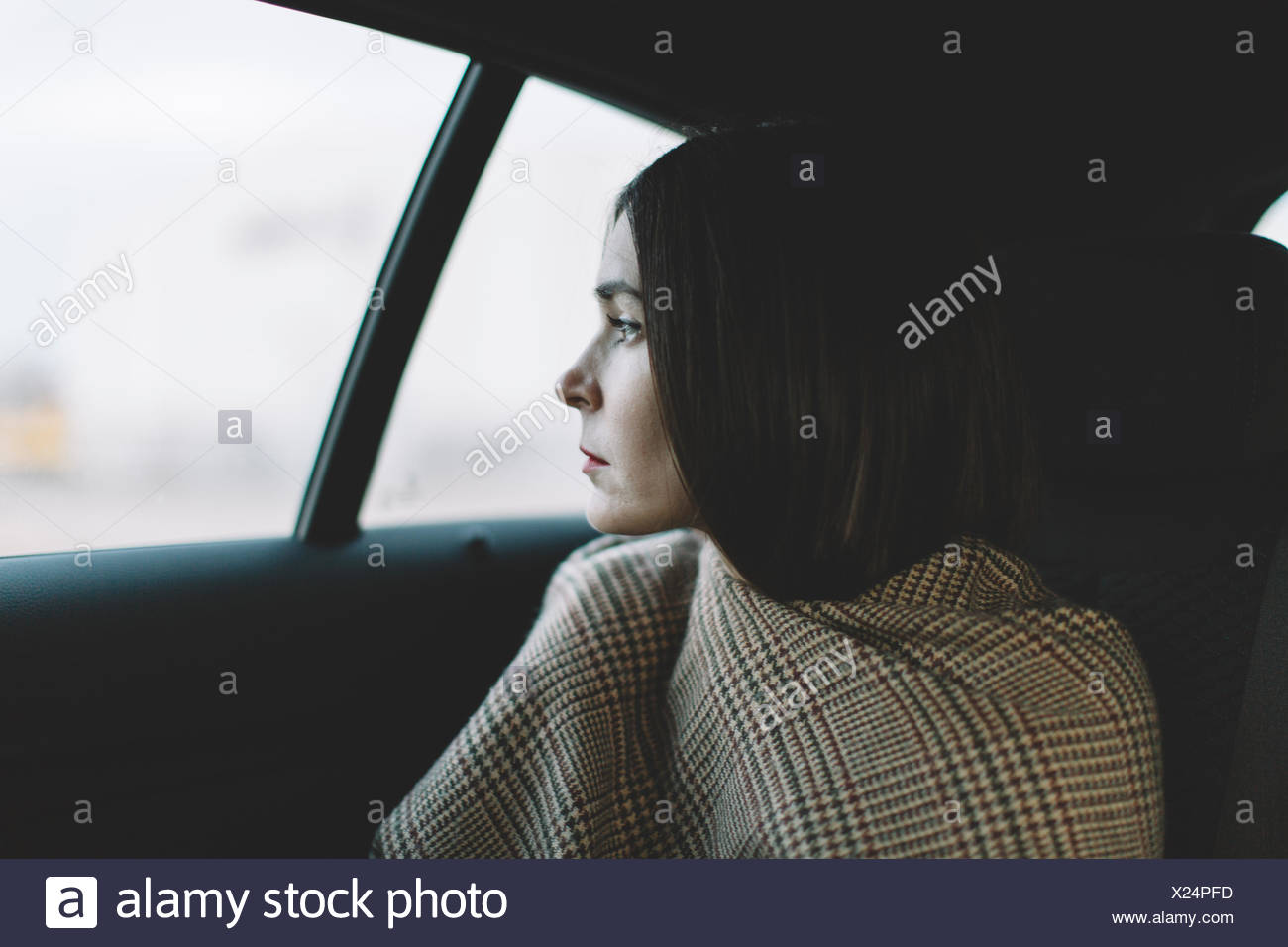 Woman sitting in car looking through the window - Stock Image