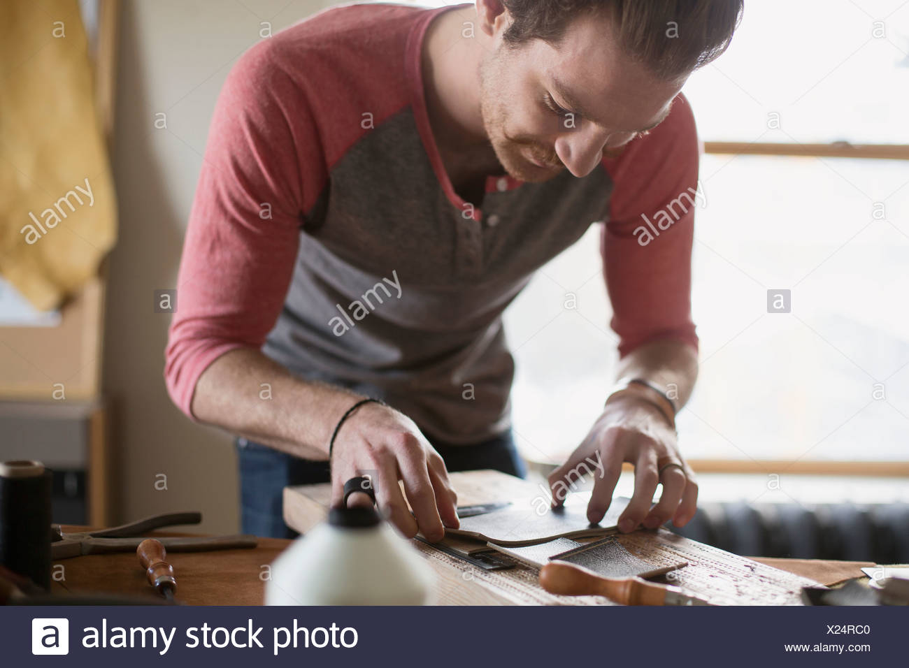Young man making leather belts at workshop - Stock Image