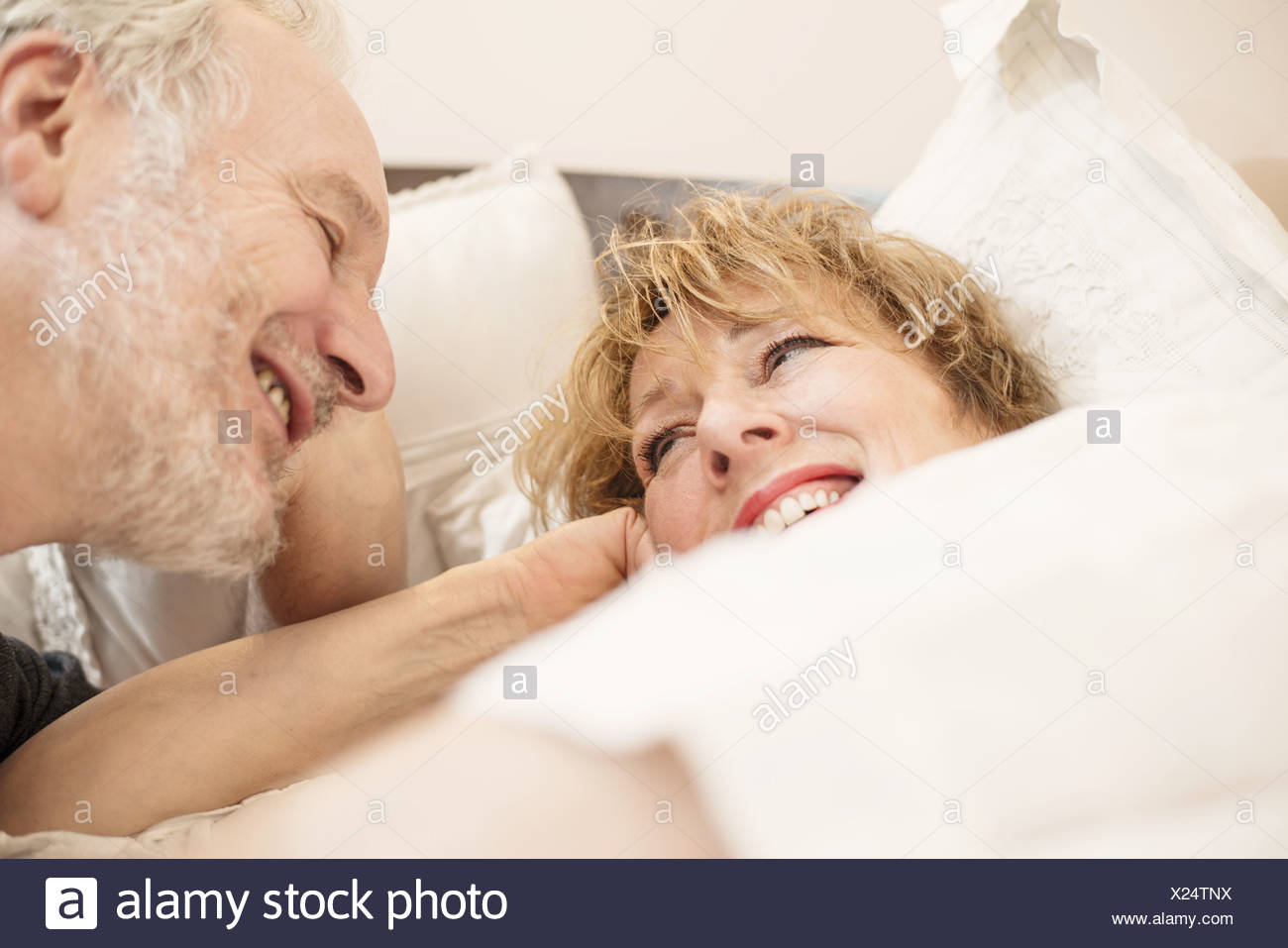 Couple in bed, smiling - Stock Image