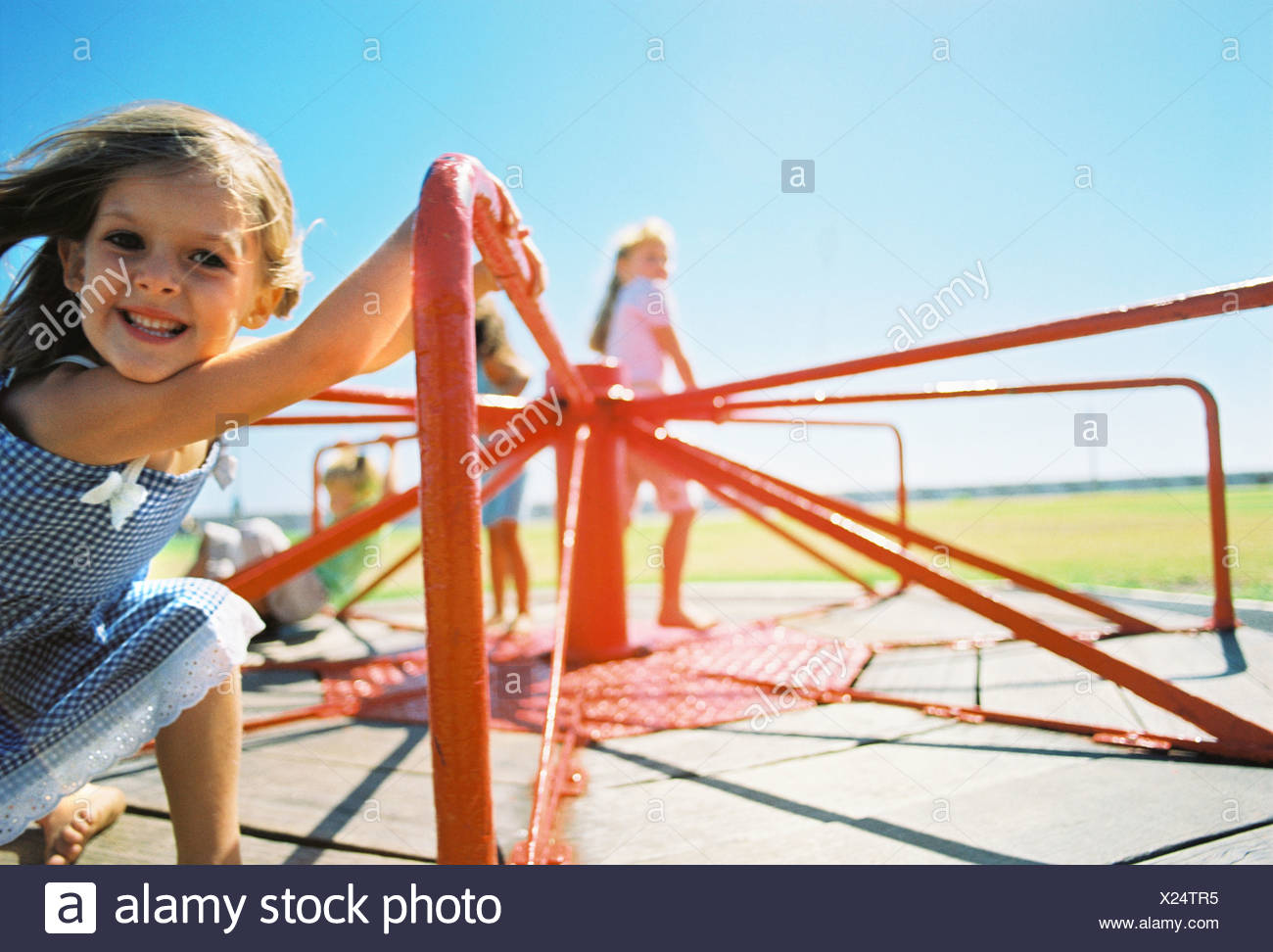 Children riding on playground merry-go-round - Stock Image