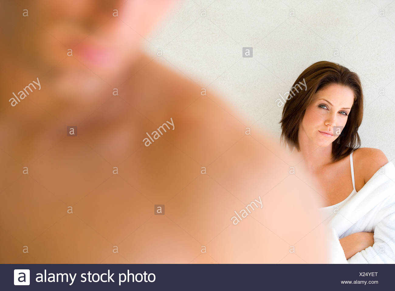 Young woman with arms folded, man in foreground differential focus - Stock Image