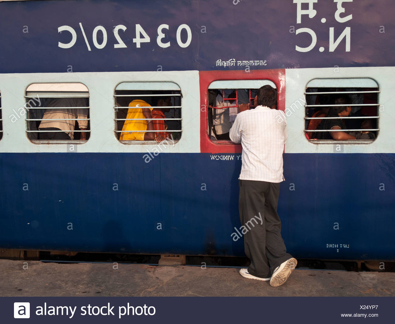 Man talking to train passenger before the train departs from New Delhi Railway Station, New Delhi, India, Asia - Stock Image