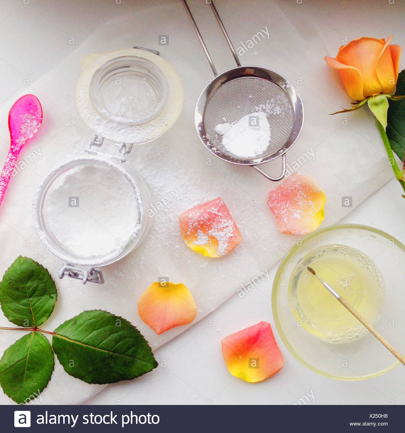 Edible flowers and icing sugar - Stock Image