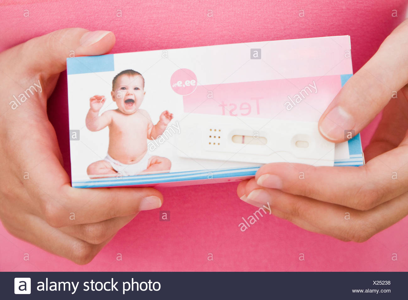 woman holding a pregnancy test - Stock Image