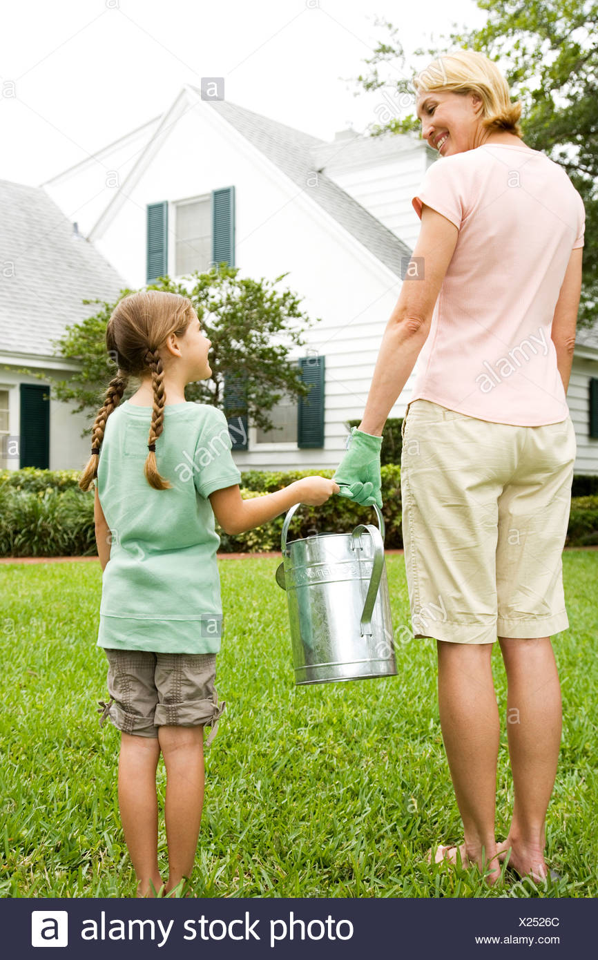 mother and daughter carrying watering can - Stock Image