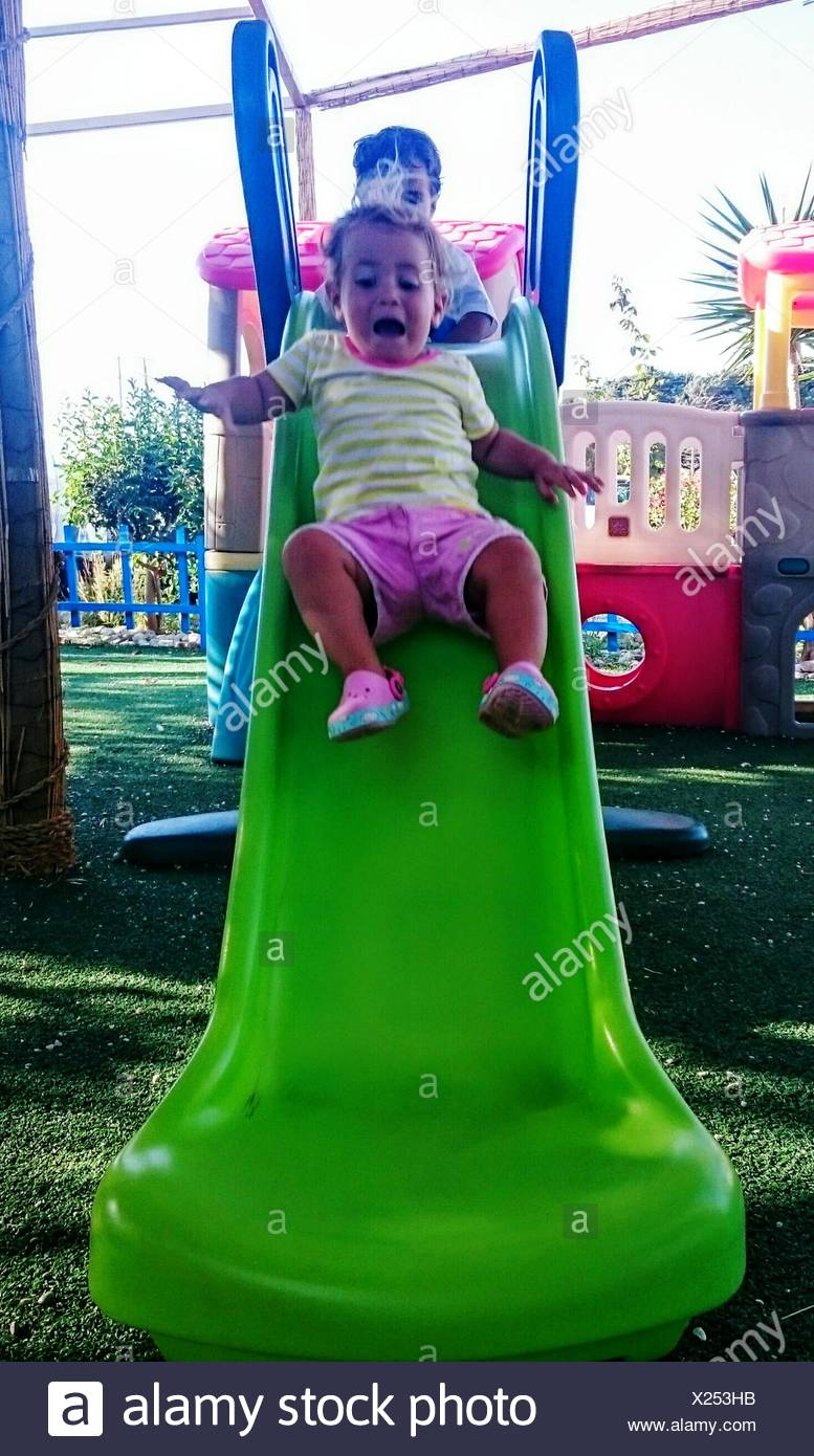 Low Angle View Of Frightened Girl On Slide At Park - Stock Image
