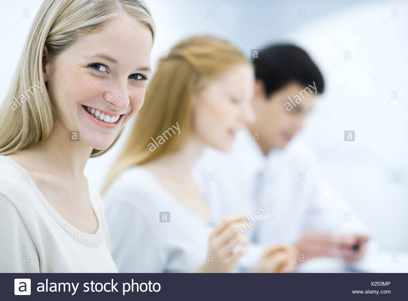 Young professional woman smiling at camera, colleagues working in background - Stock Image