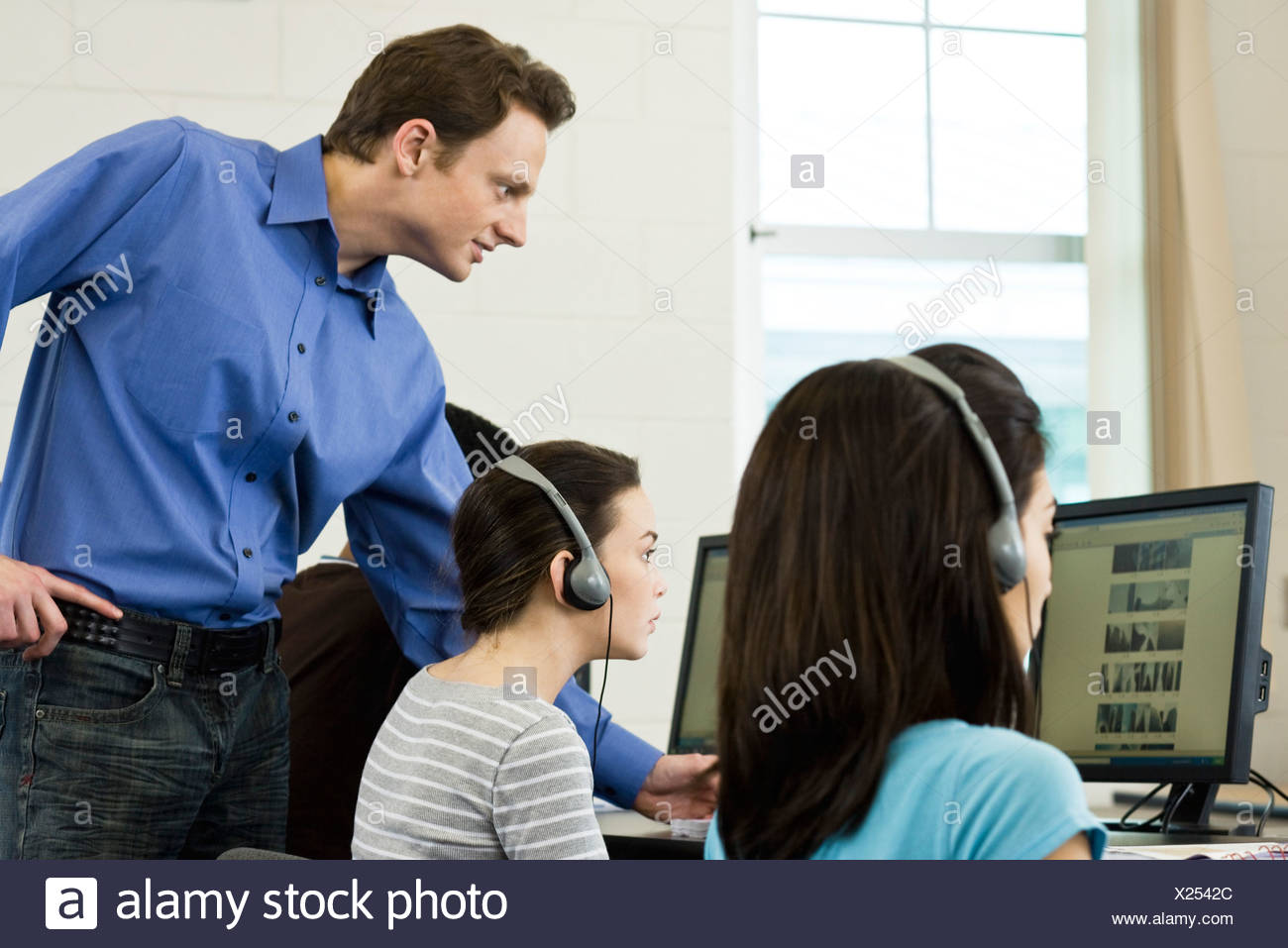 Teacher assisting high school students in computer lab - Stock Image