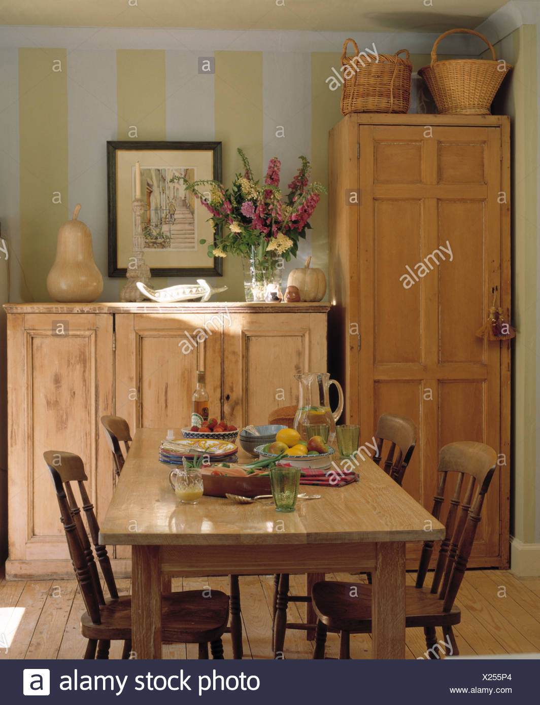 Simple wood table and old wood chairs in striped dining room ...